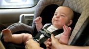 Baby in a back seat located child safety seat